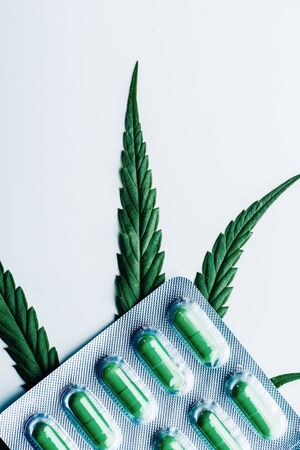 green pills in blister and marijuana on white background