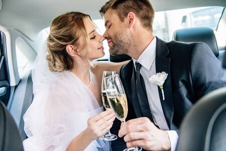 attractive bride and handsome bridegroom kissing and clinking with champagne glasses
