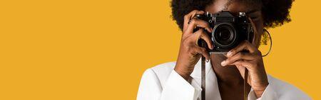 panoramiczne ujęcie kręconej afroamerykanki zakrywającej twarz podczas robienia zdjęcia na pomarańczowo