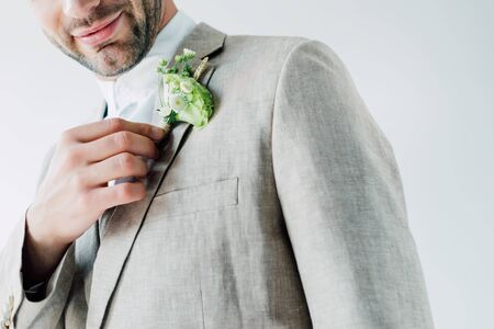 cropped view of bridegroom in suit holding floral boutonniere isolated on grey 版權商用圖片