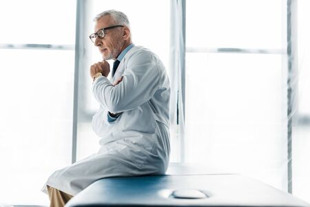 thoughtful doctor in glasses and white coat sitting on massage table and touching face 版權商用圖片