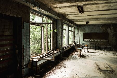 abandoned classroom with dirty chairs in school