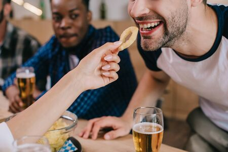 cropped view of woman feeding cheerful man with fried onion ring while sitting in pub with friends Banco de Imagens