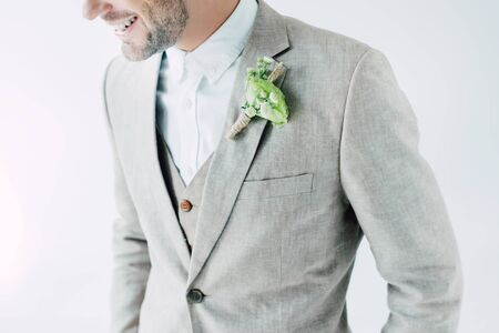 cropped view of smiling bridegroom in suit with boutonniere isolated on grey 版權商用圖片