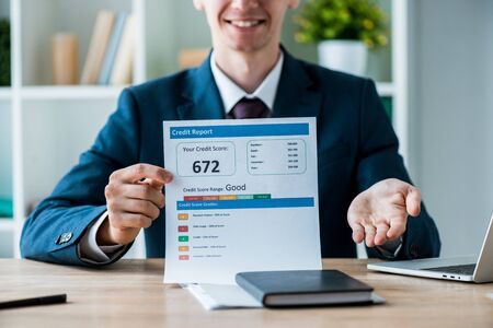 selective focus of cheerful man holding document with credit report lettering near laptop in office