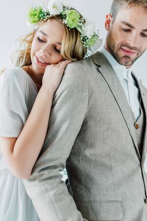 attractive bride and handsome bridegroom smiling and looking away isolated on grey