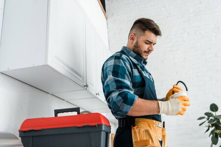 handsome bearded man holding funnel near toolbox in kitchen
