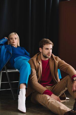 fille blonde élégante en blouson de cuir bleu assis sur une chaise près de l'homme en manteau marron