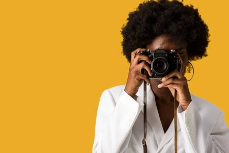 curly african american girl covering face while taking photo isolated on orange