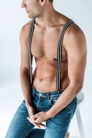 cropped view of muscular man in suspenders sitting with clenched hands on white