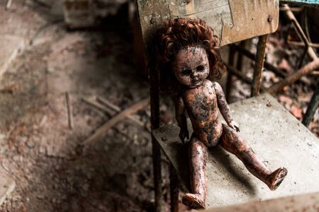 dirty and burnt baby doll on wooden chair in school 写真素材