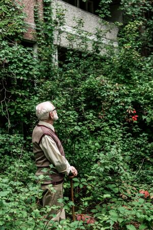 senior man in glasses looking at house overgrown with leaves
