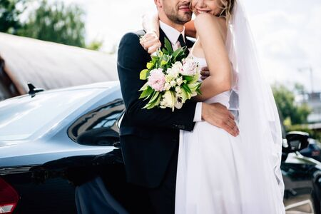 cropped view of bridegroom in suit hugging bride in wedding dress with bouquet