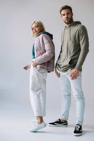 full length view of stylish blonde girl and bearded man on grey