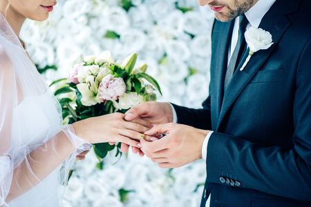 cropped view of bridegroom putting wedding ring on finger