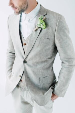 cropped view of bridegroom in suit with hands in pockets isolated on grey