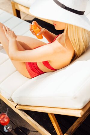 sexy young woman on lounger applying sunscreen in sunny day Stock Photo