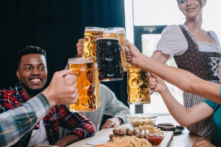 cheerful multicultural friends clinking mugs of beer while celebrating octoberfest in pub