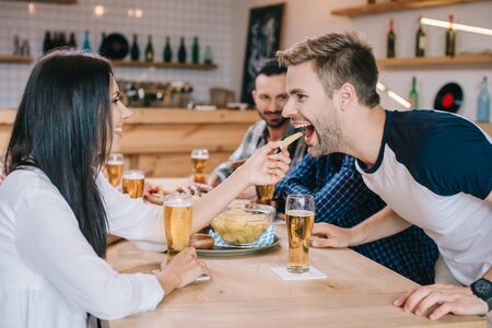 young woman feeding cheerful man with french fries while sitting in pub with friends