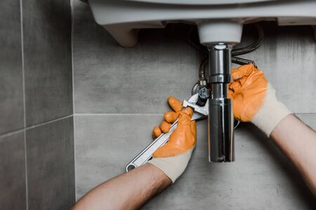 cropped view of repairman fixing water damage with adjustable wrench Stock fotó
