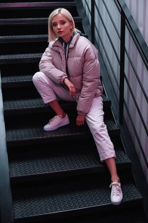 blonde girl in down jacket and sneakers sitting on stairs and looking at camera