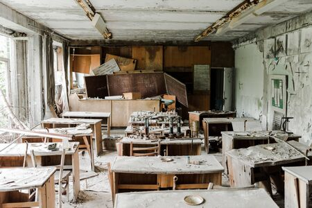 abandoned and creepy classroom with dirty tables and chalk board in school