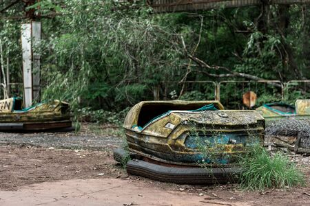 selective focus of abandoned and dirty bumper cars in amusement park