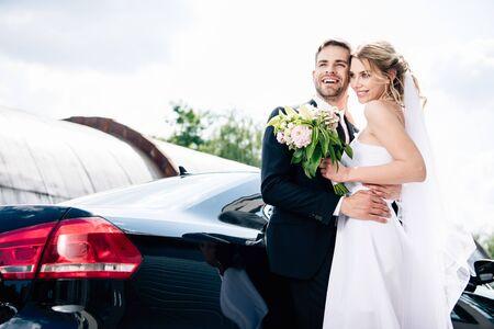 handsome bridegroom in suit hugging attractive and blonde bride with bouquet