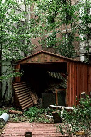 metallic garage near green trees and building