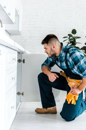 side view of handsome handyman with tool belt sitting near kitchen cabinet Stockfoto