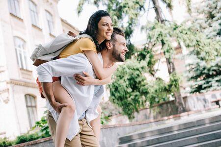 happy bearded man piggybacking girl near building