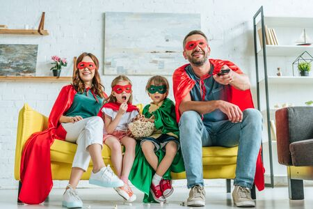 happy family in costumes of superheroes watching tv while sitting on sofa with popcorn
