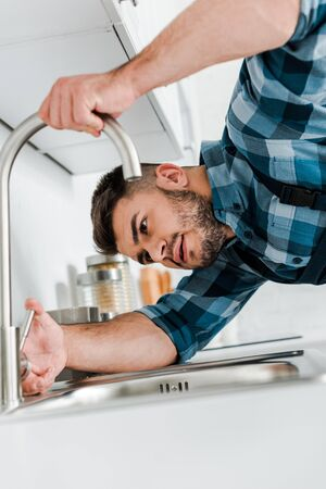 selective focus of bearded handyman working near sink in kitchen