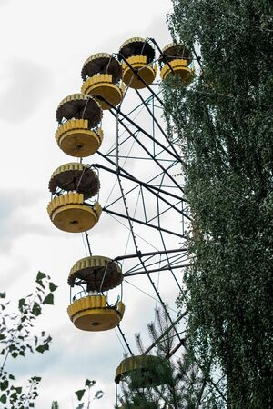 rusty yellow ferris wheel in amusement park in chernobyl