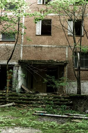 abandoned brown building with mold on stairs near green trees in chernobyl