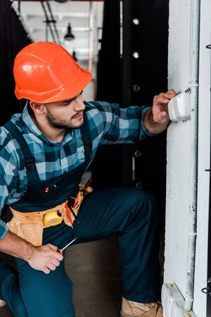 handsome bearded worker in safety helmet touching light switch