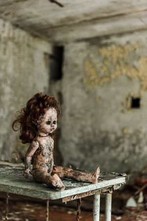 abandoned and burnt baby doll on dirty desk