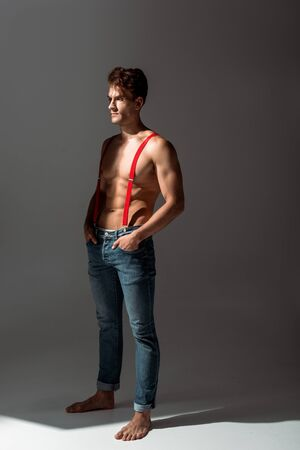 shirtless and handsome man touching red suspenders while standing on grey Standard-Bild