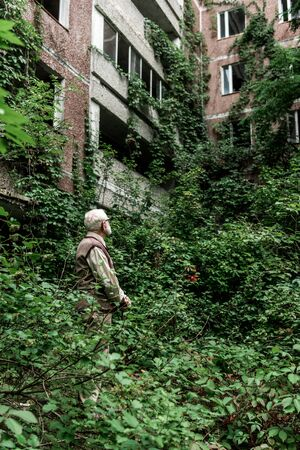 retired man in glasses looking at house overgrown with leaves
