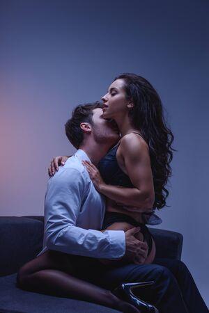 giovane uomo in camicia bianca che abbraccia e bacia la seducente fidanzata in lingerie nera e calze su sfondo viola