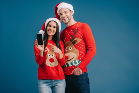 couple in santa hats and christmas sweaters pointing at smartphone with blank screen isolated on blue