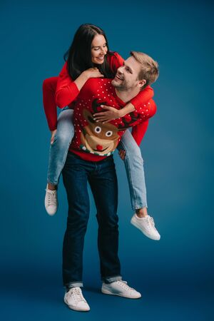 beautiful couple in christmas sweaters piggybacking isolated on blue