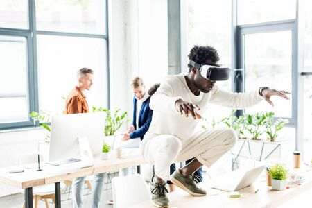 african american businessman squatting on table while using vr headset, and colleagues working in office Foto de archivo