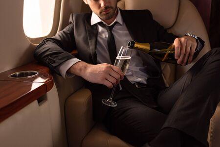 vista ritagliata dell'uomo che versa champagne nel bicchiere in aereo