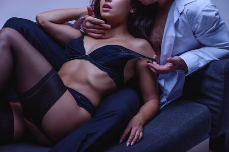 cropped view of man hugging sexy girlfriend in black lingerie and stockings while lying on couch on purple background Stock Photo