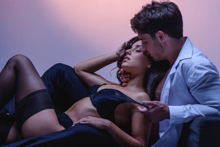 young man in white shirt embracing seductive girl in black lingerie and stockings on purple background Reklamní fotografie