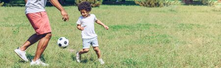 panoramic shot of african american father and son playing football in park