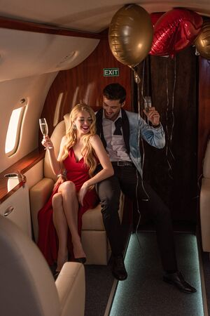 beautiful young couple with champagne sitting in airplane Archivio Fotografico