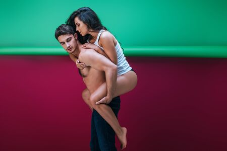 handsome shirtless piggybacking sexy girlfriend in sleeveless shirt and panties on red and green background Stok Fotoğraf