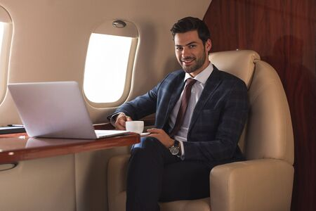 smiling businessman holding cup of coffee in plane with laptop during business trip Stock Photo
